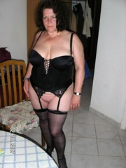 Brunette wife in black corset shows off..