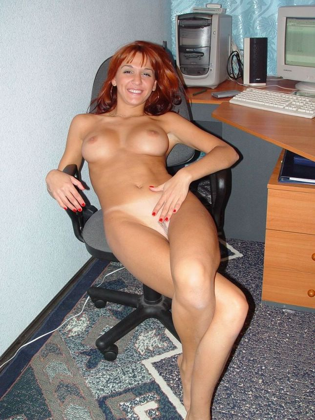 Redhead and cheerful secretary posing naked at work place and ...
